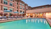 Divanes y sombrillas alineadas junto a la piscina del hotel mientras las luces de la noche destellan en el agua