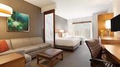 Una habitación estándar iluminada en Hyatt Place at Anaheim Resort/Convention Center con zonas de dormitorio, de estar y de trabajo separadas