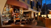 Stools line a counter as a basketball game plays on a TV in a bar at the Hyatt Regency Orange County