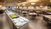 Una barra de comida con vajilla, fruta, carnes y utensilios cerca de un espacio para sentarse con mesas y sillas