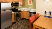 Cocina con refrigerador, estufa, microondas, fregadero, máquina lavaplatos y mesa con dos sillas
