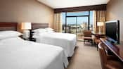 Dos camas Queen Size frente a una cómoda-escritorio con TV, además de dos sillones y un balcón