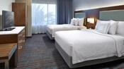 Dormitorio tipo suite Queen con dos camas Queen Size, mesa de noche y lámpara, frente a una cómoda con TV y un armario