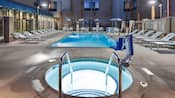 El spa y la piscina de Springhill Suites rodeados de sillas de terraza y camastros