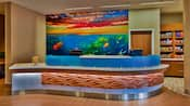The curved front desk of Springhill Suites in front of a tropical sea-themed wall mural