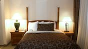 A double bed with a wooden headboard flanked by end tables with lamps