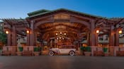 A vintage car parked at the carport and entrance to Disney's Grand Californian Hotel & Spa at night