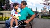 Un niño con su juguete de peluche sentado en el regazo de su papá, usando una silla de ruedas en Disneyland Park
