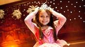 Una niña pequeña con un vestido de princesa sonríe mientras se prueba una tiara brillante