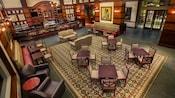 Varias mesas con sillas, sillones con mesas y sofás sobre una gran alfombra en el centro del salón