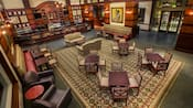 Several tables with chairs, armchairs with end tables and sofas on a large rug in the centre of the lounge