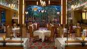 An elegant arts and crafts style dining room where tables are set with tablecloths and wine glasses