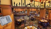 A rustic dining room and buffet decorated with cowboy sillhouettes and arts and crafts furniture