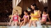 Una mamá junto a 3 niñas chapotean en el borde de la piscina