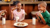 Children sitting at a table enjoy a snack of Mickey cookies and milk
