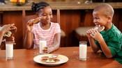 Niños sentados alrededor de una mesa disfrutando un bocadillo de leche y galletas de Mickey