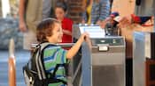 A smiling boy with a backpack at a turnstile entrance to Disney's California Adventure Park