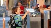 Un niño sonriente con una mochila en la entrada a Disney California Adventure Park
