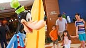 A statue of surfer Goofy greets a family of four in the lobby of Disney's Paradise Pier Hotel