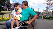 Un niño con un juguete de peluche sentado sobre el regazo de su papá, que está en una silla de ruedas en Disneyland Park