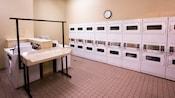 Un cuarto de lavandería amplio con lavadoras, secadoras y mesas para doblar y colgar la ropa