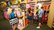 Huéspedes inspeccionan la colorida mercancía de una tienda de regalos bien surtida