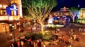 Una vista vespertina, con impresionante iluminación, de una plaza en Downtown Disney District donde los Visitantes disfrutan de la música