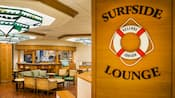A sign for Surfside Lounge at its entrance with a seating area and bar in the background