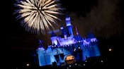 Fuegos artificiales estallan en el cielo nocturno sobre Sleeping Beauty Castle