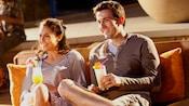 Una pareja con cocteles sentada en un sofá de mimbre al aire libre, mira una película