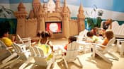 Kids watch a Disney cartoon while sitting in beach chairs at Paradise Theater