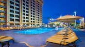 A calm rooftop pool surrounded by lounge chairs at Disney's Paradise Pier Hotel