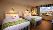Two queen beds with beach ball pillows, lamps, end table, mounted mirror, desk, chair and window with Disney California Adventure Park view