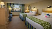 Dos camas Queen Size con mesita de noche al centro, escritorio con silla, armario con centro de entretenimiento y un sofá que se convierte en dos camas Twin Size