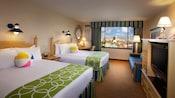 Dos camas Queen Size con cabeceras de madera, un escritorio, una cómoda con televisión y un sofá, además de una ventana