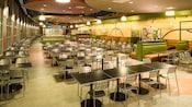 Uma área de refeições com decoração moderna, mesas, cadeiras, cabines, obras de arte e iluminação superior