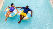 A man and a woman, in separate inner tubes, hold hands as they float down Castaway Creek