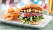 Ahi tuna burger with cucumber-mango salsa, watercress, garlic aioli and potato chips