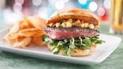 Ahi tuna burger with cucumber-mango salsa, watercress, garlic aioli and potato chips