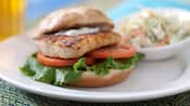 Mahi mahi on bun with tomato and lettuce with bowl of coleslaw in background