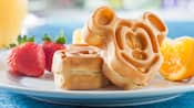 A Mickey Mouse shaped waffle propped up by another waffle on a plate with strawberries and an orange wedge