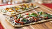 Chicken flatbread pizza and vegetable flatbread pizza on a wooden board
