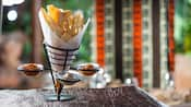A cone-like metal holder with slices of crisp African breads and 3 dipping sauces