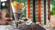 un sostenedor de metal como un cono con rodajas de panes crujientes africanos y 3 cazuelas de salsa