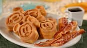 Slices of bacon on a plate with waffle bites that resemble Mickey Mouse