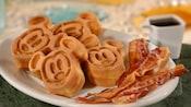Rodajas de tocineta en un plato con bocados de waffle que se asemejan a Mickey Mouse
