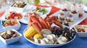 Plate of crab legs, clams, muscles, corn on the cob and potatoes, next to other plates of food