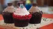 3 cupcakes de chocolate, 1 con glaseado blanco y chispas rojas, cubierto con una imagen de Mickey Mouse