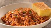 A bowl of jambalaya served with a piece of cornbread