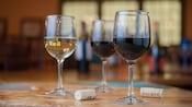 Una copa de vino blanco y 2 copas de vino tinto, junto a 2 corchos